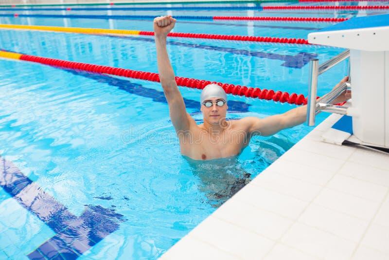 De zwemmer van de sport het winnen De mens die toejuichend het vieren overwinningssucces glimlachen gelukkig in pool het dragen z royalty-vrije stock afbeeldingen