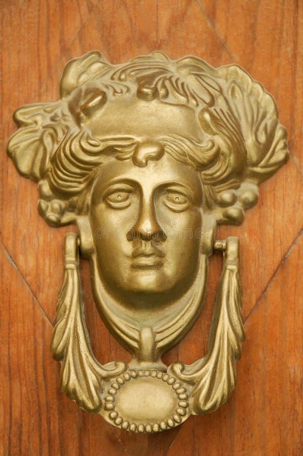 Dea greca che batte sulla porta di legno immagini stock