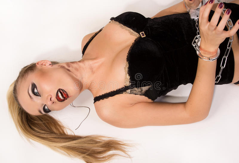 Dead blonde in the handcuffs lying on the floor stock photography