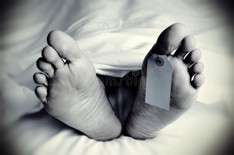 Dead body with a blank toe tag, in monochrome royalty free stock image