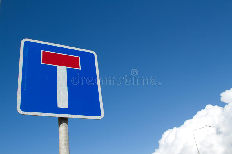 Dead end. A square sign with the symbol for 'dead end' on blue with white border against a blue sky with clouds royalty free stock photos