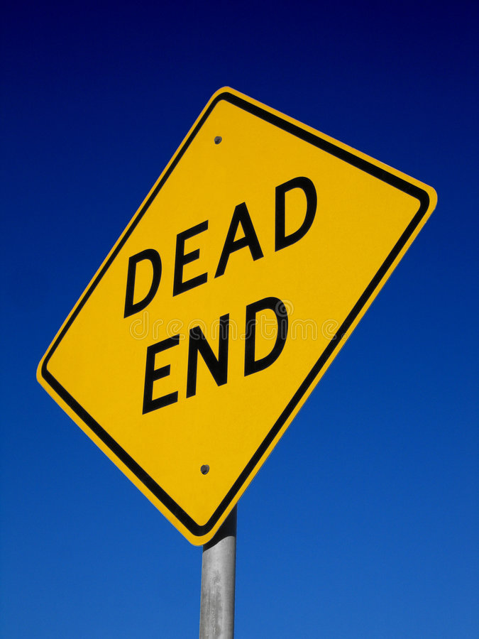 Dead End Sign. Photo of a bright amber dead end sign lit by the morning sun against a deep blue sky stock image