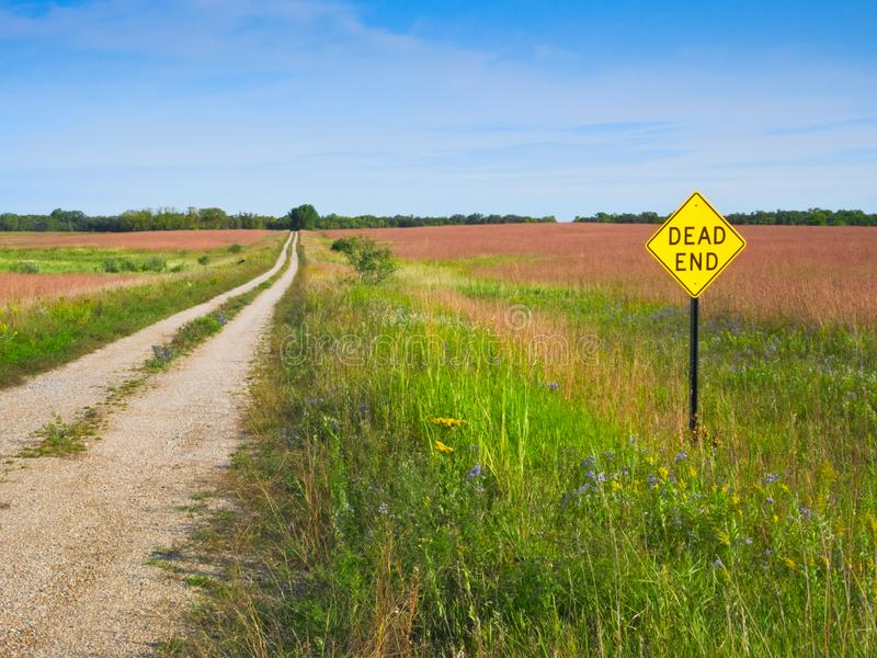 A Dead End sign posted along a rural gravel road. A Dead End sign posted along a rural gravel road on a sunny day royalty free stock image