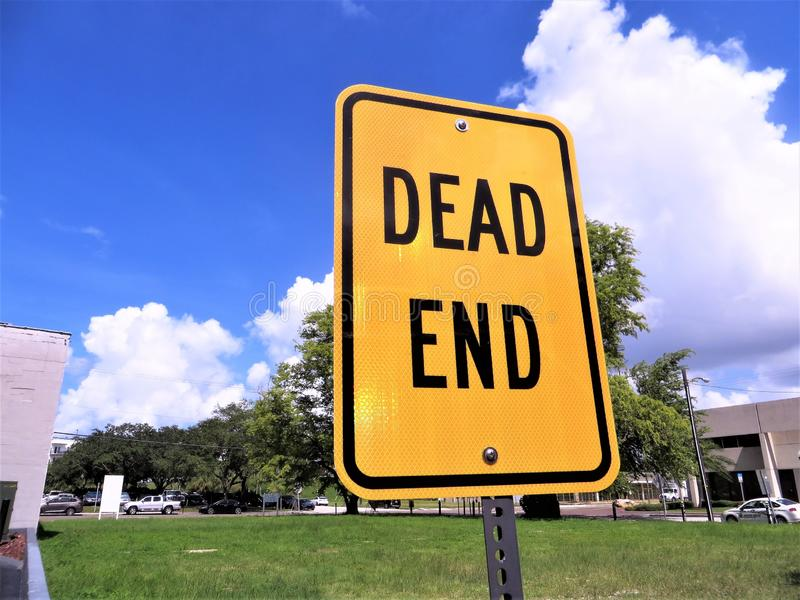 Dead End warning sign. Dead end sign in front of small urban greenspace with trees, blue sky and billowing clouds in background on a sunny August day in Florida royalty free stock photography