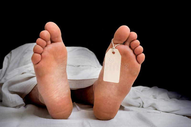The dead man`s body with blank tag on feet under white cloth. In a morgue royalty free stock photos