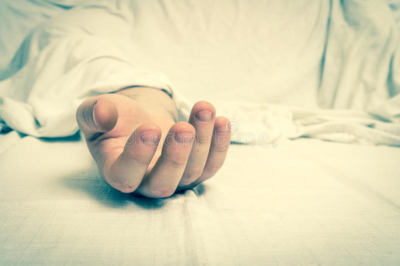The dead man`s body under white cloth with focus on hand royalty free stock image