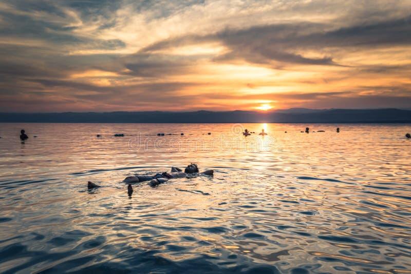 Dead Sea - 05 oktober 2018: Turister som badar i Salty Dead Sea vid solnedgång, Jordanien royaltyfri fotografi