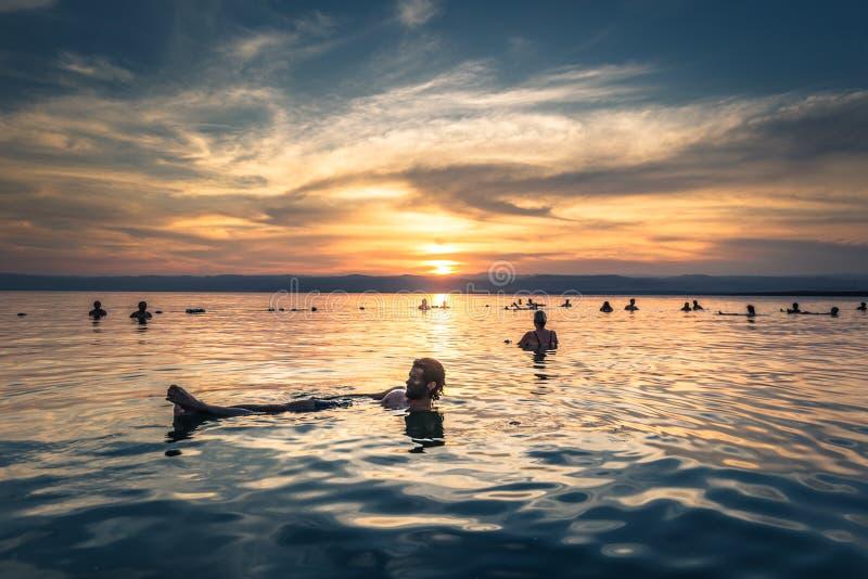 Dead Sea - 05 oktober 2018: Turister som badar i Salty Dead Sea vid solnedgång, Jordanien arkivbilder