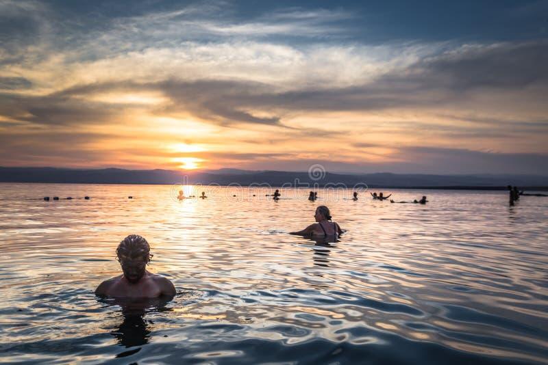 Dead Sea - 05 oktober 2018: Turister som badar i Salty Dead Sea vid solnedgång, Jordanien royaltyfri foto