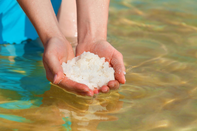 Dead Sea salt in hands. Female hands with sea salt from Dead Sea stock image