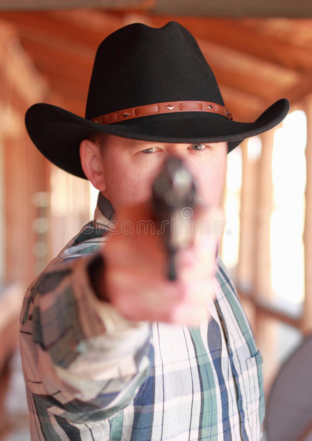Dead Serious Cowboy. Serious cowboy aiming pistol at camera stock photos