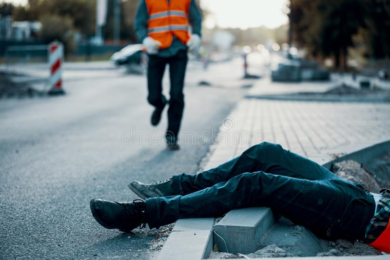 Dead victim during roadworks. Non-compliance with health and safety regulations royalty free stock image
