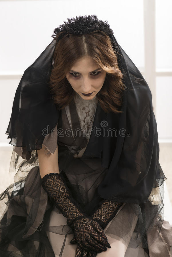 Dead widow in grief. Young beautiful demonic female. Dark Beautiful Gothic Princess.Halloween party stock photos