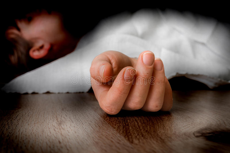 Dead woman lying on the floor under white cloth stock image