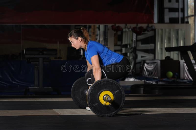 做与重的杠铃的年轻女人deadlift锻炼在黑暗的健身房 库存图片