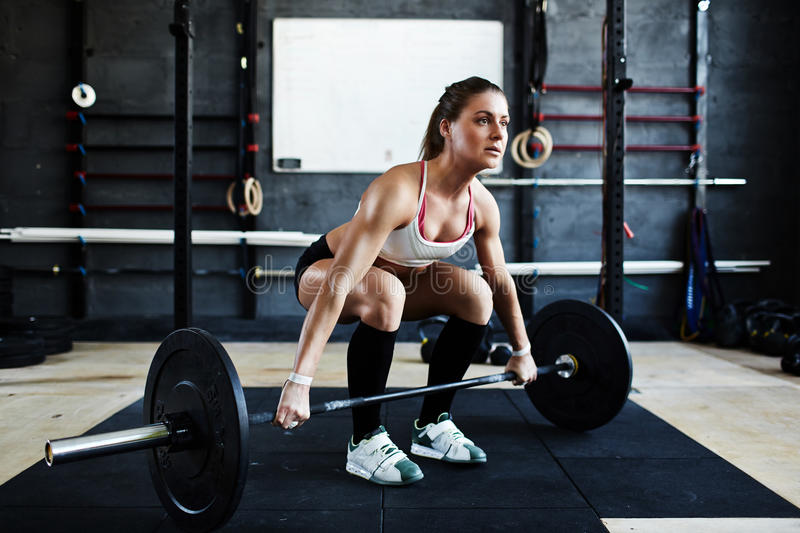 Deadlifts in Crossfit Gym. Intense crossfit workout in dark gym: bodybuilder woman ready to pick up heavy barbell with effort standing in squatting stance royalty free stock photos