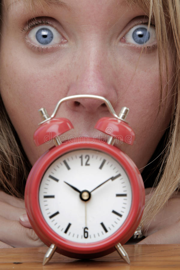 Deadline. Woman with red alarm clock representing lateness or a deadline royalty free stock photography