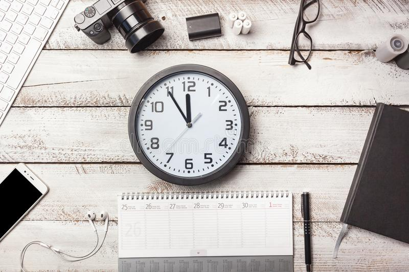 Deadline clock on photographer desk with white wood boards royalty free stock image