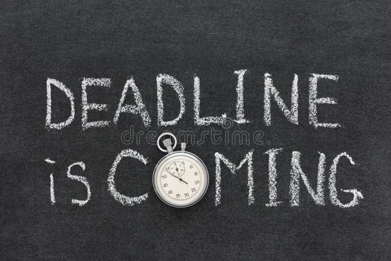 Deadline coming. Deadline is coming phrase handwritten on chalkboard with vintage precise stopwatch used instead of O royalty free stock image