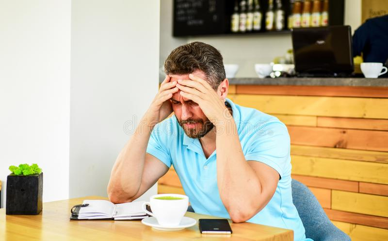Deadline coming search ideas need inspiration. Man disappointed desperate face sit cafe with mug of coffee and notepad. Headache and stress. Crisis in stock photography