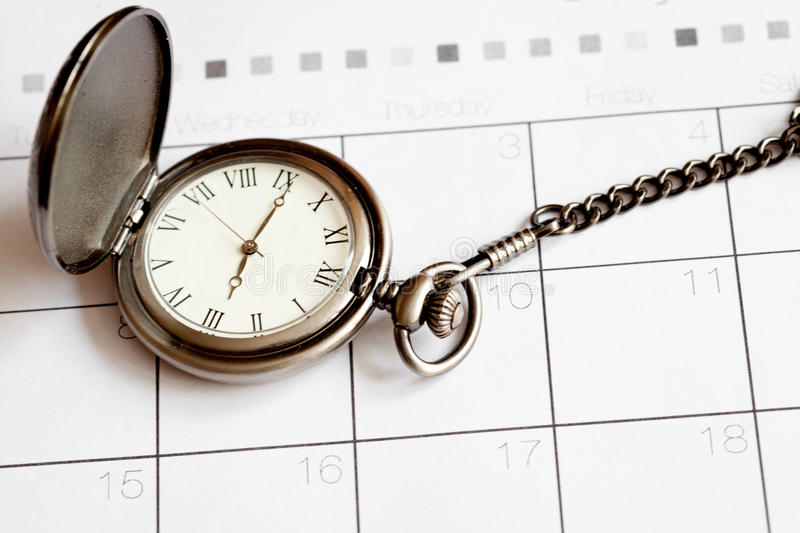 Deadline concept pocket watch on calendar background. Close up royalty free stock images