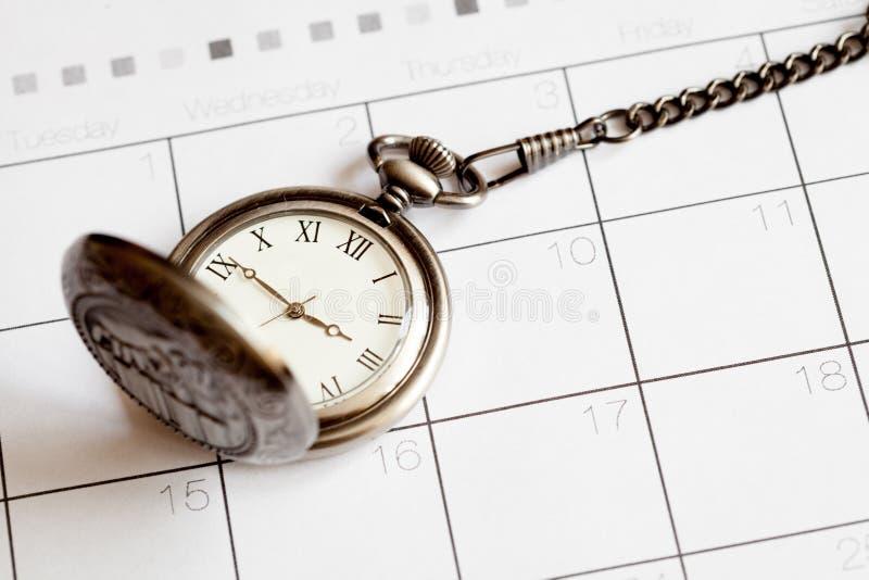 Deadline concept pocket watch on calendar background. Close up stock photos