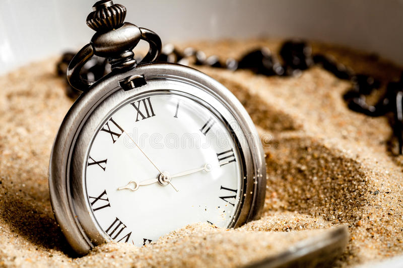 Deadline concept pocket watch in sand background. Close up royalty free stock images