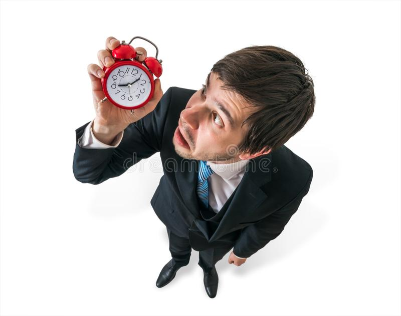 Deadline concept. Young stressed businessman is looking at clock. royalty free stock photos
