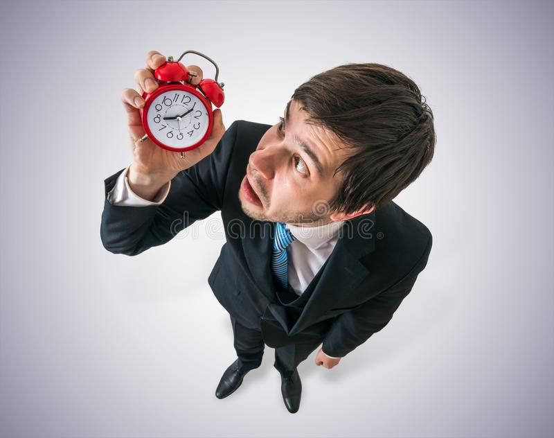Deadline concept. Young stressed man is looking at clock and have to hurry. stock photography