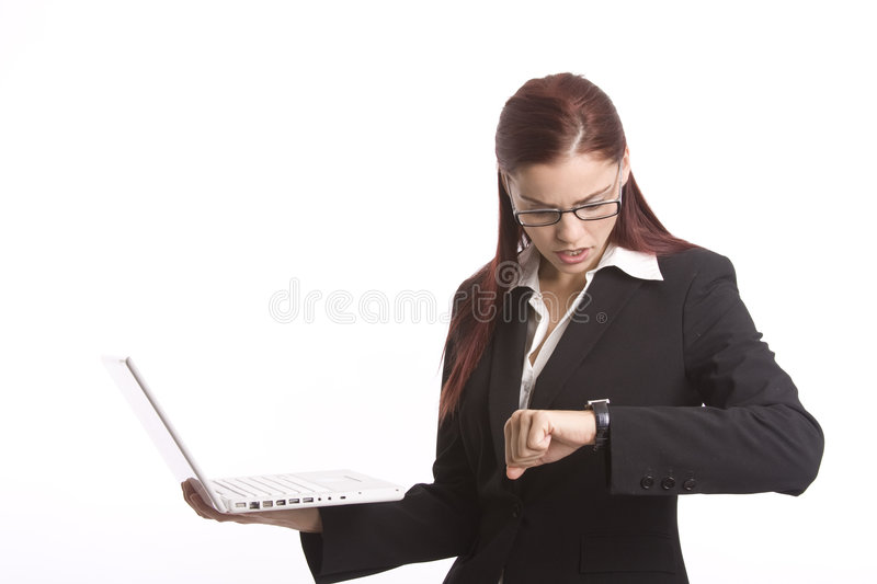 Deadline looming. Woman worker checking her watch as she holds a laptop computer royalty free stock photos