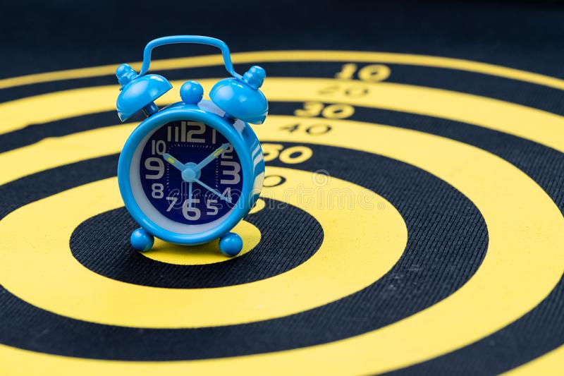 Deadline, time management or goal and target with time specific concept, retro blue alarm clock on yellow circle dartboard royalty free stock photography
