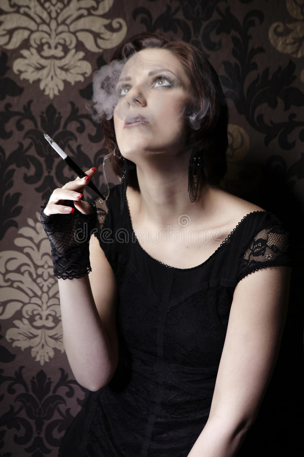Deadly smoke. Young woman on indoor location posing as drug addict. Female smoking cigarettes stock photo
