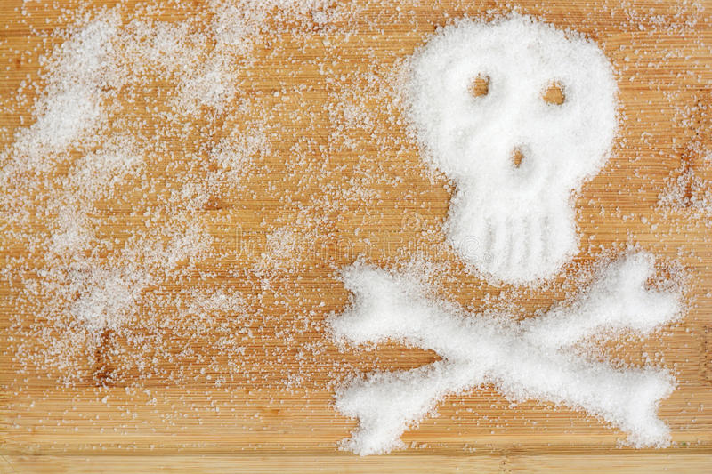 Deadly sugar addiction suggested by spilled white sugar crystals forming a skull on a wooden table stock photos