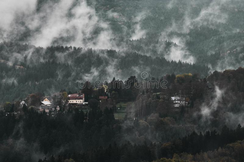 Deadpan dark misty rainy morning landscape with the sand rocky montains in Czech Saxon Switzerland in autumn colors. Deadpan dark misty rainy morning landscape royalty free stock photography