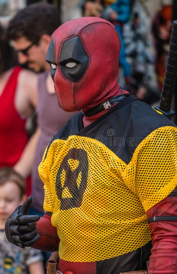 Deadpool character on a street. Man dressed as Deadpool character in costume promoting comic shop royalty free stock image