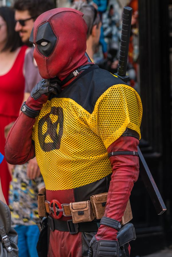Deadpool character on a street. Man dressed as Deadpool character in costume promoting comic shop stock photography