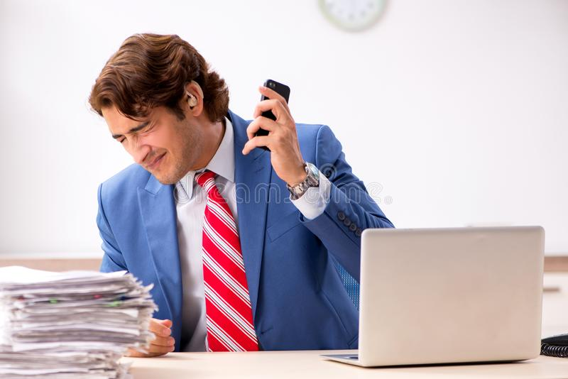 The deaf employee using hearing aid in office stock photos