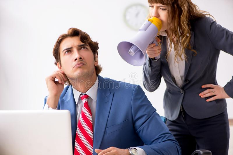 The deaf employee using hearing aid talking to boss royalty free stock image