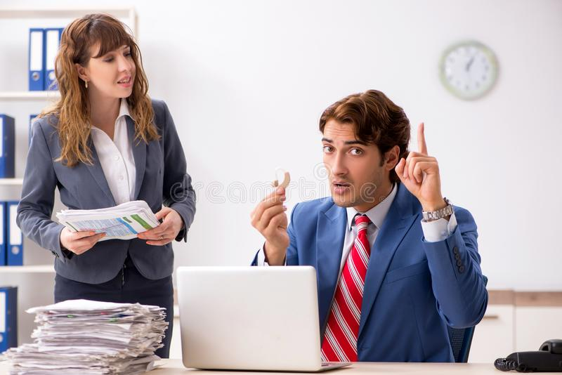 Deaf employee using hearing aid talking to boss stock photos