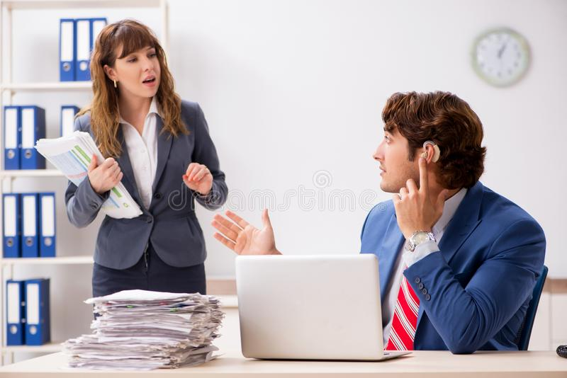 The deaf employee using hearing aid talking to boss royalty free stock photo
