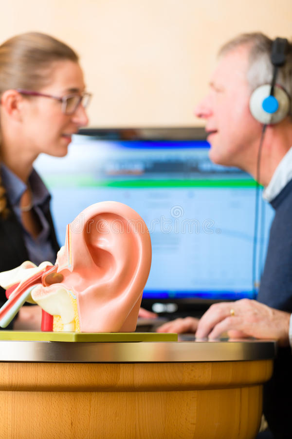 Deaf man makes a hearing test. Older men or pensioner with a hearing problem make a hearing test and may need a hearing aid, in the foreground is a model of a stock image