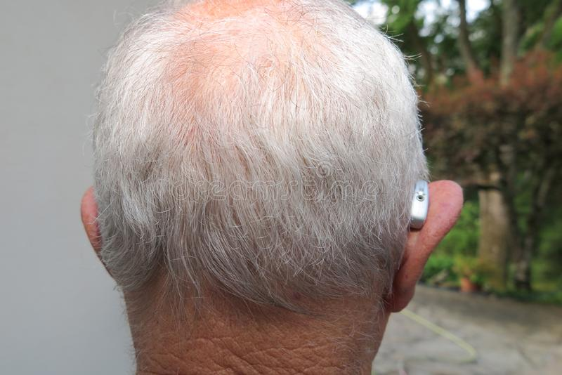Senior citizen man wearing modern digital high technology hearing aid in ear back view royalty free stock photography