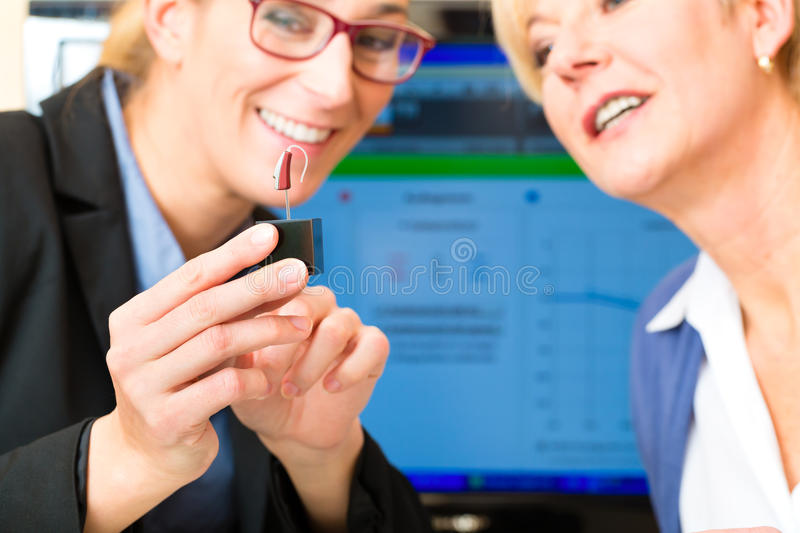 Deaf woman makes a hearing test. Older women or female pensioner with a hearing problem make a hearing test, the accoustician holding a model of a hearing aid royalty free stock photography
