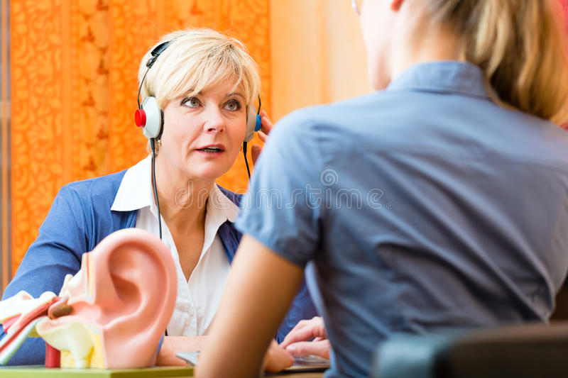 Deaf woman takes a hearing test. Older women or female pensioner with a hearing problem make a hearing test and may need a hearing aid, in the foreground is a stock images