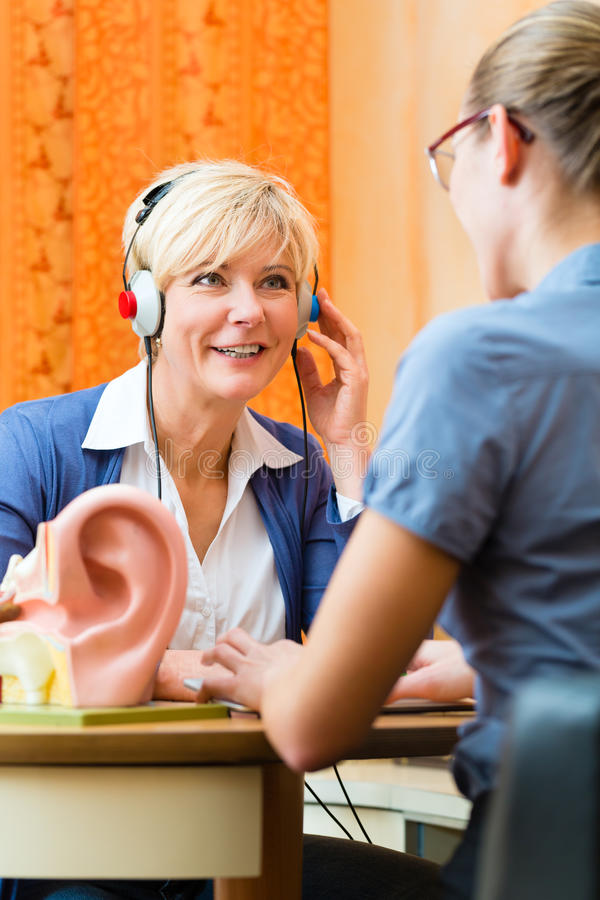 Deaf woman takes a hearing test. Older women or female pensioner with a hearing problem make a hearing test and may need a hearing aid, in the foreground is a royalty free stock photo