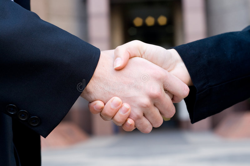 Deal. Close up of business man and woman shaking hands in front of a corporate building making a business deal royalty free stock photos
