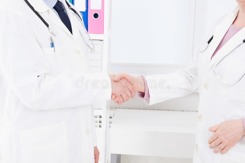 Deal. Concept of collaboration in medicine. Close up photo of two doctors shaking hands.Medical insurance. Deal Concept of collaboration in medicine. Close up royalty free stock photography