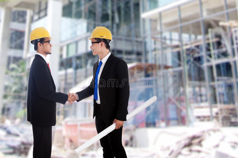 Deal of two engineers. Two engineers closing a deal by handshake in front of a building site royalty free stock photos