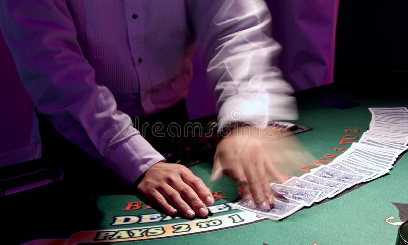 The Dealer. Card dealers are quick and shuffle cards with precision. In this image only the dealers left hand moves royalty free stock photography