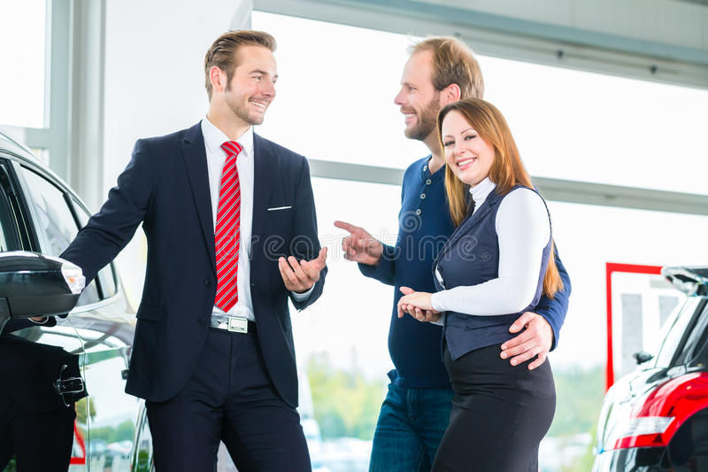 Dealer, clients and auto in car dealership. Seller or car salesman and clients or customers in auto dealership presenting the interior decoration of new and used royalty free stock photo